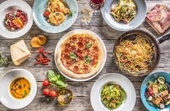 Spitze der vollen Tabelle der Ansicht der italienischen Mahlzeiten auf Platten und Wanne Pizzateigwaren Risottosuppe und Gem?sesa lizenzfreie stockfotos