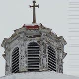 Spitze des alten Kirchenkirchturms gegen grauen Winterhimmel Lizenzfreie Stockfotos
