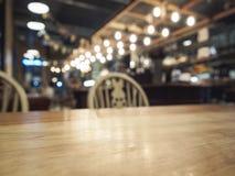 Spitze des Holztischs mit unscharfem Barrestauranthintergrund Lizenzfreie Stockfotografie