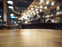 Spitze des Holztischs mit unscharfem Barrestauranthintergrund Lizenzfreie Stockfotos
