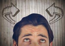Spitze des Männerkopfs gebogene Pfeile betrachtend gegen undeutliche Täfelung Lizenzfreies Stockbild
