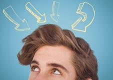 Spitze des Männerkopfs gelbe Pfeile betrachtend gegen blauen Hintergrund Stockbild