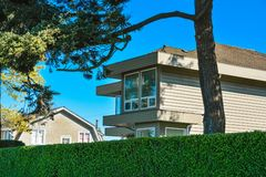 Spitze des Wohnhauses über grüner Hecke auf Hintergrund des blauen Himmels stockbild