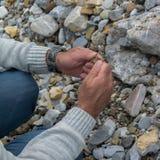 Spitze hinunter die Ansicht der Mannhand Mineralien erforschend Geologische Besetzung in der Natur stockfotografie