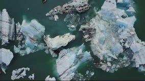 Spitze hinunter Vogelperspektive von den Gletschereisbergen, die in Lagune in Island schwimmen stock footage