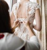 Spitze-Hochzeitskleid der Braut wei?es Brauthilfe gesetzt auf das Heiratskleid lizenzfreie stockfotos
