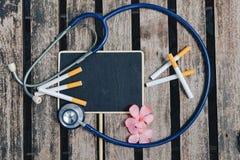 Spitze legen Ansicht, Stethoskop, Zigarette, Signage und Blume auf hölzernen Hintergrund Lizenzfreie Stockfotos