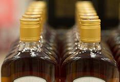 Spitze von Plastikflaschen mit dem Kognak oder Weinbrand, die im Spirituosenladen stehen Von der Front Stockfotos