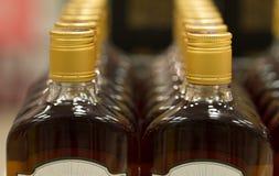 Spitze von Plastikflaschen mit dem Kognak oder Weinbrand, die im Spirituosenladen stehen Von der Front Stockfotografie