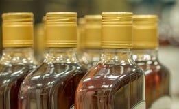 Spitze von Plastikflaschen mit dem Kognak oder Weinbrand, die im Spirituosenladen stehen Von der Seite Stockfotografie