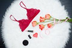 Spitzen- BH Burgunders auf weißem Pelz Orange Rosen, Lippenstift und candl stockbilder
