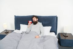 Spitzen für früh aufwachen Bärtiges schläfriges Gesichtsbett des Mannes mit Wecker im Bett Welche schrecklichen Geräusche Stellen lizenzfreie stockfotografie