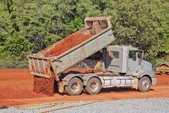 Spitzen Sie den LKW, der Schmutz auf einer Baustelle ausgibt Lizenzfreie Stockfotos