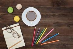 Spitzen-viev auf einer Kaffeetasse, Makronen, färbte Bleistifte und ein noteb Lizenzfreies Stockfoto
