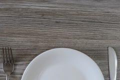 Spitzenhälfte der weißen leeren Platte, des Messers und der Gabel auf grauem hölzernem Vorsprung Stockfotografie