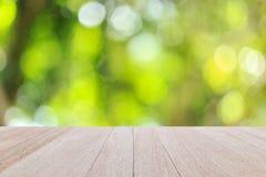 Spitzenholztisch mit sonnigem abstraktem grünem Naturhintergrund, Querstation Stockfotos