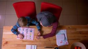 Spitzenschuß der moslemischen Mutter im hijab Buchstaben mit ihrem kleinen Sohn am Tisch zu Hause lernend stock footage