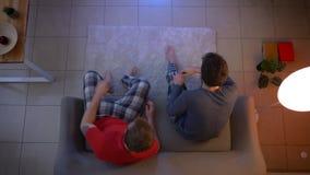Spitzenschuß von zwei jungen Kerlen im Sleepwear, der im Sofa und in Verbindung stehendem aufpassendem Fernsehen im Wohnzimmer si stock video footage