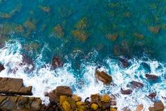 Spitzenvogelperspektive des Blaus bewegt das Zusammenstoßen auf felsiger australischer Küstenlinie wellenartig Stockfotografie