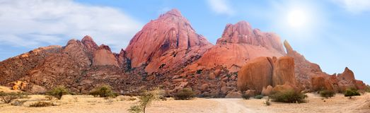 Spitzkoppe mountains range panoramic view on blue sky, clouds and bright sun background, mountain panorama landscape, Namibia royalty free stock photography
