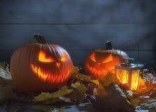 Spöklik lykta för pumpastålarnolla bland torkade sidor på trästaketet Arkivfoto