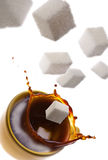 Splash. High angle view of sugar cubes falling into a cup of coffee Stock Photos