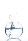 Splash. Bowl with water and a splash on white background royalty free stock photo