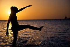Splash!. Pregnant woman splashes in the water, silhoutted at sunset Stock Photos