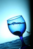Splash. A blue glass reflecting a blue water Royalty Free Stock Image
