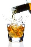 Splash. Double whiskey being poured into a glass against white background Royalty Free Stock Images
