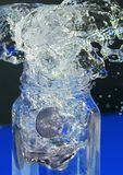 Splash. Water splashing out of a bottle as coins dropped into it Stock Photography