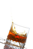 Splash. A splash into a whiskey glass reflected on white background Royalty Free Stock Images