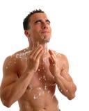 Splash. A muscular young man splashing water on his face Royalty Free Stock Photos