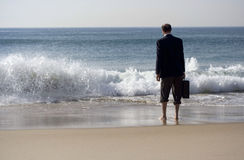 Splash. Businessman walking barefoot in the ocean with briefcase in hand, dreaming of his future royalty free stock photo