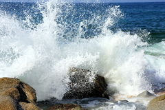 Splash. Of the wave with blue sky and stones Stock Photography