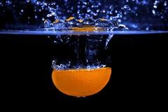 Splash. Orange fruit falling into water stock photos