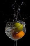 Splash. Lemon and orange splashing into a glass of water Royalty Free Stock Photo