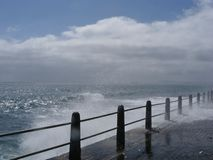 Splash. Atlantic waves splashing against a concrete walkway at Sea Point, Cape Town Royalty Free Stock Photo