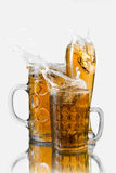 Splash beer in glasses Royalty Free Stock Photography