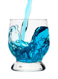 Splash, blue drink is being poured into glass Royalty Free Stock Image