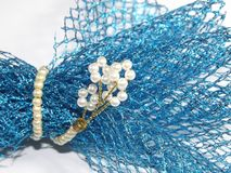 A splash of blue lace wrapped by pearls royalty free stock photos