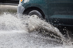 Splash by a car as it goes through flood water Stock Photography