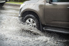 Splash by a car as it goes through flood water.  Royalty Free Stock Image