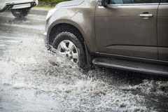 Splash by a car as it goes through flood water Royalty Free Stock Image