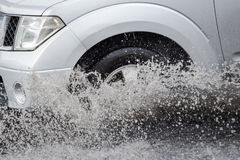 Splash by a car as it goes through flood water Stock Images
