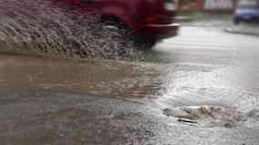 Cars drive on a flooded road in the rain, slow motion. Splash by car as it goes through flood water after heavy rains. Flooded city road with big puddle of stock video