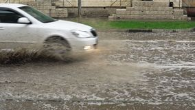 Cars drive on a flooded road in the rain, slow motion. Splash by car as it goes through flood water after heavy rains. Flooded city road with big puddle of stock video footage