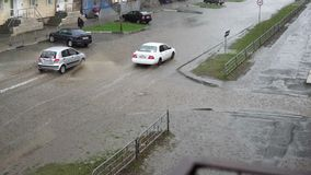 Cars drive on a flooded road in the rain, slow motion. A splash from cars as they pass through flood water after heavy rains. Flooded city road with big puddle stock footage