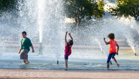 Children Playing in a Fountain  Stock Photos
