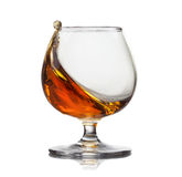 Splash of cognac in glass isolated on white Stock Images